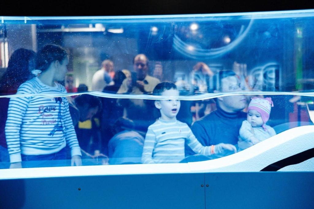Удивлённый мальчик смотрит на аквариум